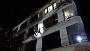 Catwoman Ines Weber spielt Saxophon während sie sich an einer Hausfassade abseilt